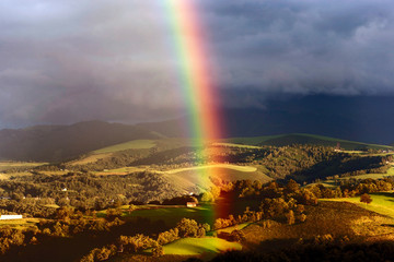 Breathtaking rainbow emerging in Southern France landscape - Pyrenees countryside near Lourdes