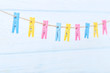 Colorful clothespins hanging on wooden background
