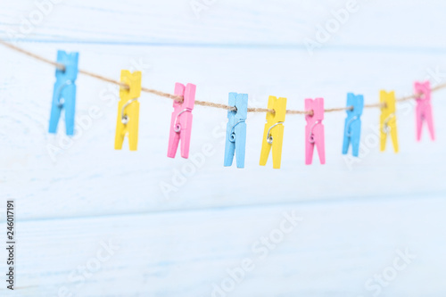Leinwandbild Motiv Colorful clothespins hanging on wooden background