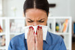 Unhealthy young woman sneezing in a tissue in the living room at home.