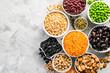Leinwandbild Motiv Selection of legumes - beans, lentils, mung, chickpea, pea in white bowls on stone background