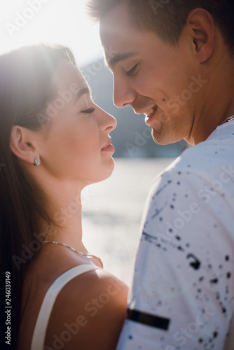 Close up man kissing his woman while walking outdoors in the city street. Beautiful summer day