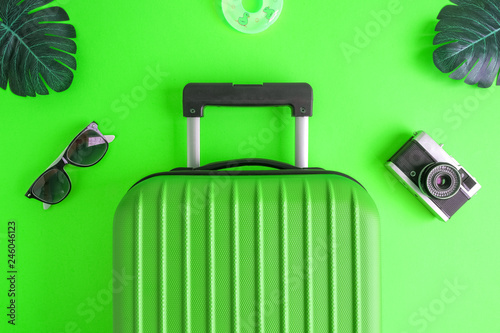 Luggage with summer vacation accessories on green. - 246046123