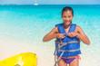 Watersport fun on Caribbean summer beach vacation. Woman tourist going on kayak tour activity on ocean, wearing life jacket.