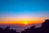 Orange sun sets on the horizon over the purple sea
