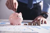 Businessman putting coin in a piggy bank. Saving money