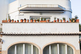 Facade with balconies and a lot of flower pots. Architectural detail. - 246168779