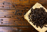 roasted coffee beans on paper on rustic wooden table, beans around scattered