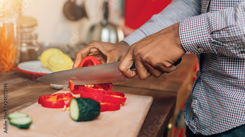 African-american man cutting bell pepper in kitchen - 246175146