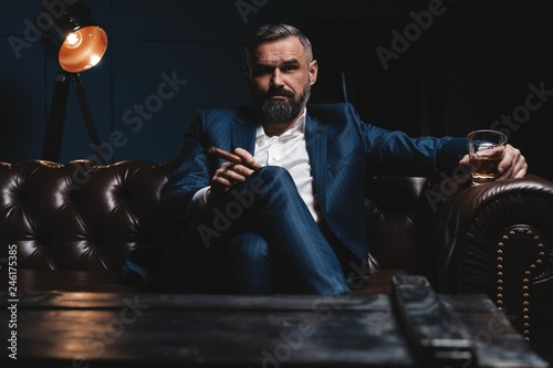 Leinwanddruck Bild Attractive man with cigar and a glass whiskey