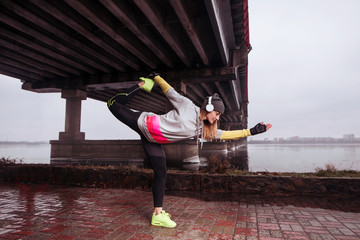 Young healthy woman doing exercises before the morning jog. Woman listening to music motivating with headphones. Under the bridge