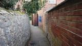 Walking through an old English alleyway - 246195965