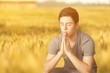 Young man praying against grey background