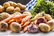 Assortment of fresh vegetables on wooden table. Carrot parsnip garlic celery onion and kohlrabi