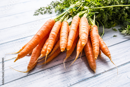 Foto Murales Bunch of fresh carrot on wooden table