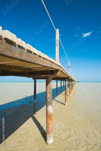 Wooden pier from beach on tropical sea - 246218199