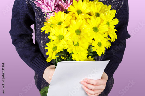 Boy holds a bouquet of yellow and pink chrysanthemums and empty greeting card in his hands. Flowers and gift for mom. © katiko2016