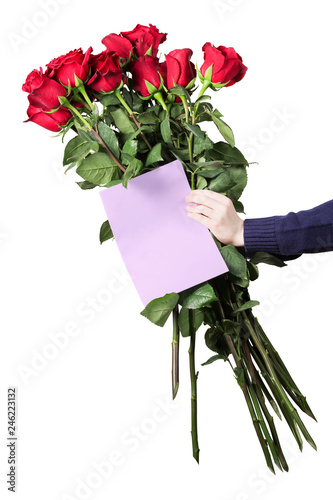 Boy holds a large bouquet of red roses and empty greeting card in his hands. Flowers for mom. Holiday greeting concept. Isolated on white background. © katiko2016