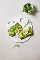 Vegan sandwiches with sliced avocado and lemon on rye bread, arugula salad served on ceramic board over white marble background. Flat lay, space