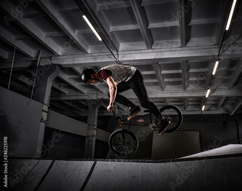 Bmx freestyle. Young BMX making tricks on his bicycle in skatepark indoors