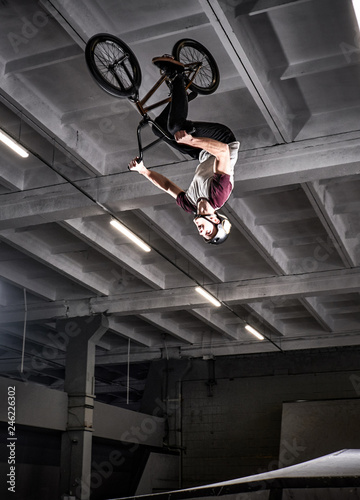 Young BMX making crazy tricks on his bicycle in skatepark indoors. Bmx freestyle.