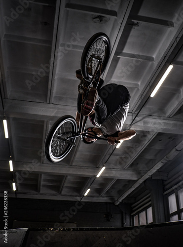 Professional BMX rider in protective helmet performing tricks in skatepark indoors
