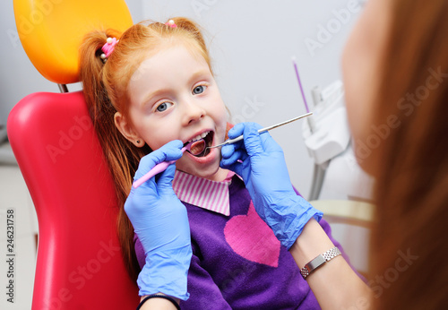 fototapeta na ścianę the child is a little red-haired girl smiling sitting in a dental chair. Pediatric dentistry, baby teeth
