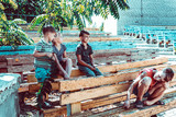 Orphaned children sit in an abandoned park on old benches