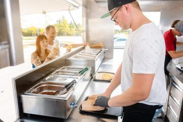 Junge Köche im Food Truck machen Essen für ihre wartenden Kunden