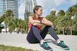Young sporty woman resting outdoors in city after run