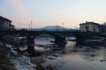 Gray, winter arched bridge in the commune of Barghe