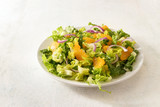 healthy salad from tangerines and lettuce with red onions on a white plate, bright background with large copy space