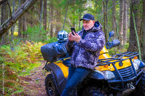 Driver ATV. Traveler in the forest. A man paves the route for travel. Navigation in the forest. Tourist paves the route on the phone. Maps navigation on mobile devices. ATV