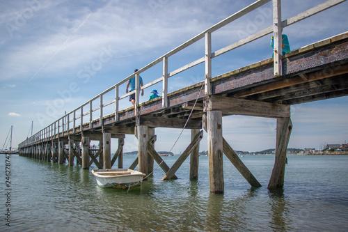 pier over the ocean with boat © Lauren