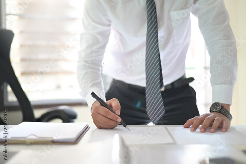 Cropped shot of businessman signing contract making a deal on office workplace. © sodawhiskey