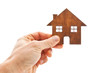 Man's hand holds wooden flat house on the white background