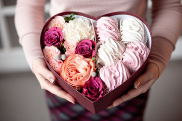 Pink and white marshmallows gift and flowers in heart shaped box with female hands