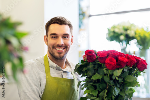 Foto Murales small business, sale and floristry concept - happy smiling florist or seller with bunch of red roses at flower shop