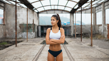 Motivated young female athlete taking a break during outdoor running workout at abandoned industrial ruins.