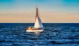 ein Segelboot segelt bei Sonnenuntergang übers Meer - 246383706