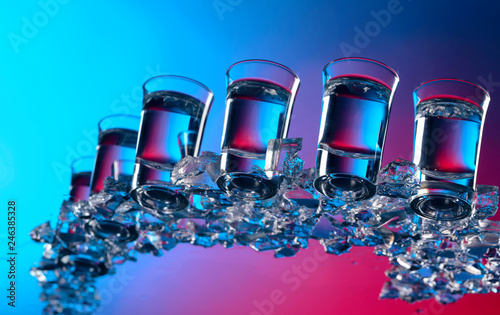 Glasses of vodka with ice on a glass table. © Igor Normann