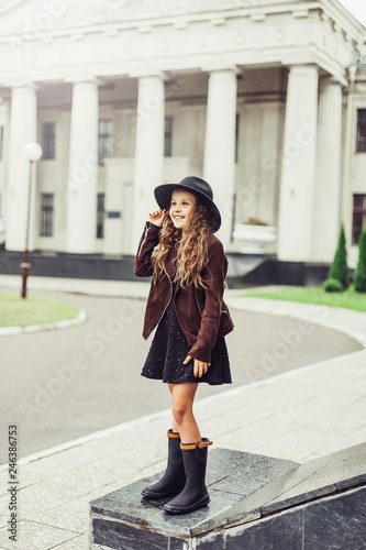 fototapeta na ścianę Outdoor portrait of teenage girl in stylish look, in black hat posing outdoors in park