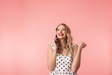 Beautiful young blonde woman wearing dress standing