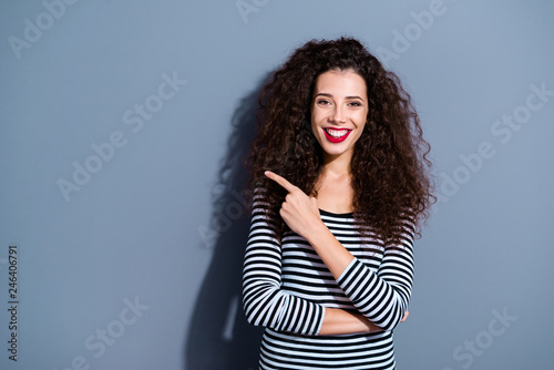 Leinwandbild Motiv Portrait of her she nice-looking cute fascinating attractive lovely cheerful cheery wavy-haired lady in striped pullover pointing aside ad isolated over gray pastel background