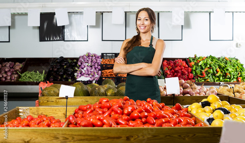 Woman in apron selling organic tomatoes in shop