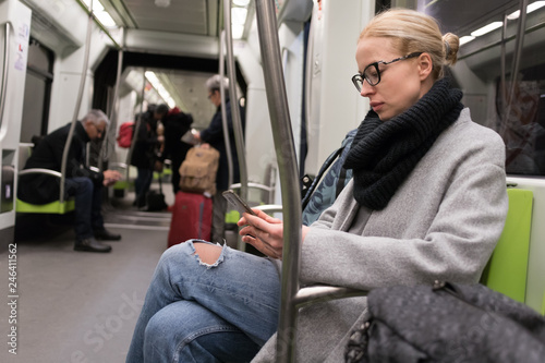 Leinwanddruck Bild Beautiful blonde caucasian woman wearing winter coat and scarf reading on the phone while traveling by metro. Public transport.