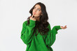 Beautiful thinking young woman dressed in green sweater posing isolated over white wall background.