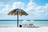 Beautiful tropical island feeling, two lounge chairs standing underneath a straw umbrella in Varadero, Cuba