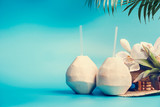 Fresh tropical coconut cocktail with drinking straws and palm leaves and flowers standing on blue turquoise background. Summer tropical vacation,travel and holiday concept