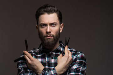 Bearded young man in plaid shirt holding Barber scissors and straight razor, near his face isolated on dark background.